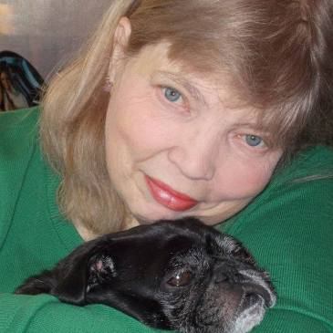 Author Jean Rabe snuggles with her black pug, Mr. Wrinkles