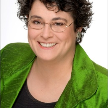 Author photo of mystery author Donna Andrews. A smiling Andrews sports a short haircut and glasses. She's wearing an emerald green blouse over a black shell.
